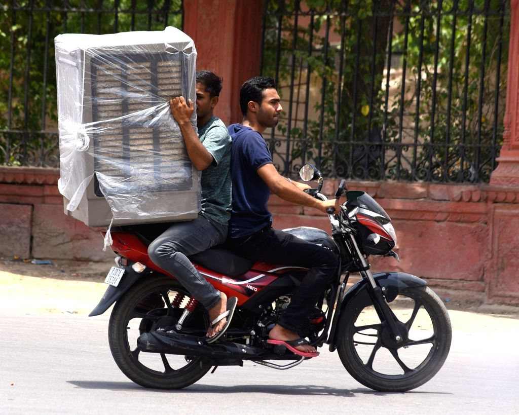 A man holds a newly bought cooler while being driven on a two-wheeler, on a hot sunny day, in Bikaner on May 23, 2018.