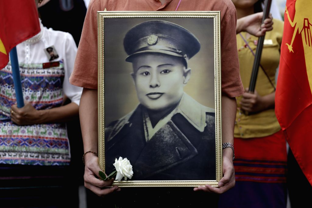 A man holds General Aung San's portrait to pay respect during the 68th Martyrs' Day ceremony in Yangon, Myanmar, July 19, 2015. Myanmar held a ceremony here Sunday ...