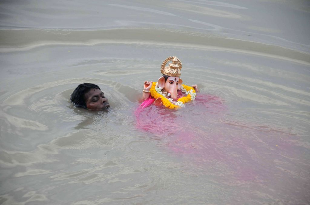 A man immerses a Ganesh idol in the Hooghly river in Kolkata on Aug 31, 2014.