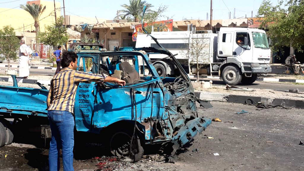 A man inspects a damaged car after an airstrike by the Iraqi Air Force in Islamic State militants-seized city of Fallujah, some 50 km west of Baghdad, Iraq, on ...