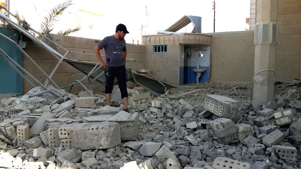 A man inspects a destroyed building after an airstrike by the Iraqi Air Force in Islamic State (IS) militants-seized city of Fallujah, some 50 kilometers west of ...