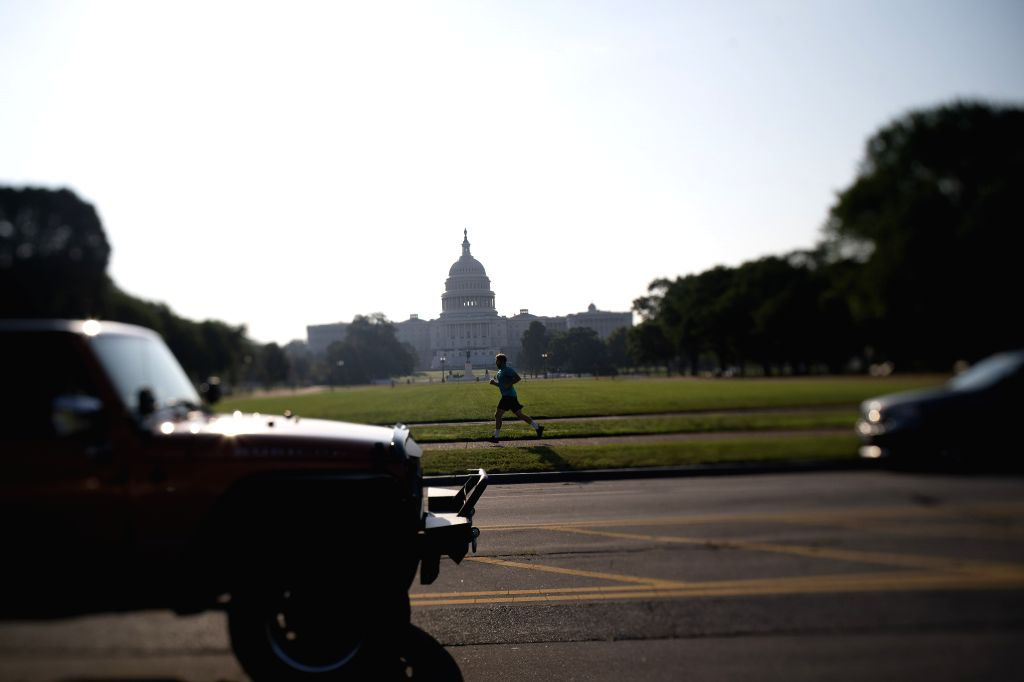 A man jogs near the Capitol Building in Washington, D.C., the United States, July 8, 2020. The number of COVID-19 cases in the United States surpassed the 3 ...