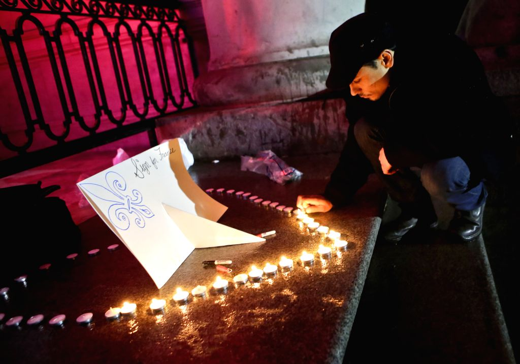 A man lights up candles at the silent vigil to commemorate the victims of Friday's terror attacks in Paris at Vancouver Gallery in Vancouver, Canada, Nov. 14, ...