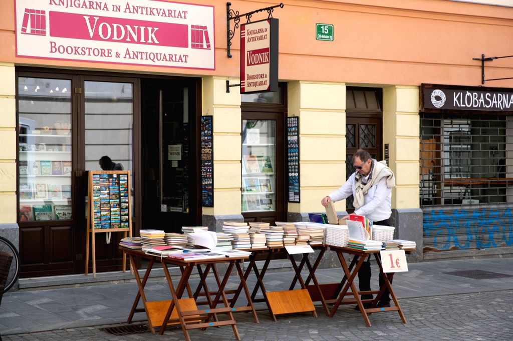 A man looks at a book in front of a bookstore in Ljubljana, Slovenia, on May 8, 2020. Slovenia's COVID-19 death toll has risen to 100 after one more patient died on ...