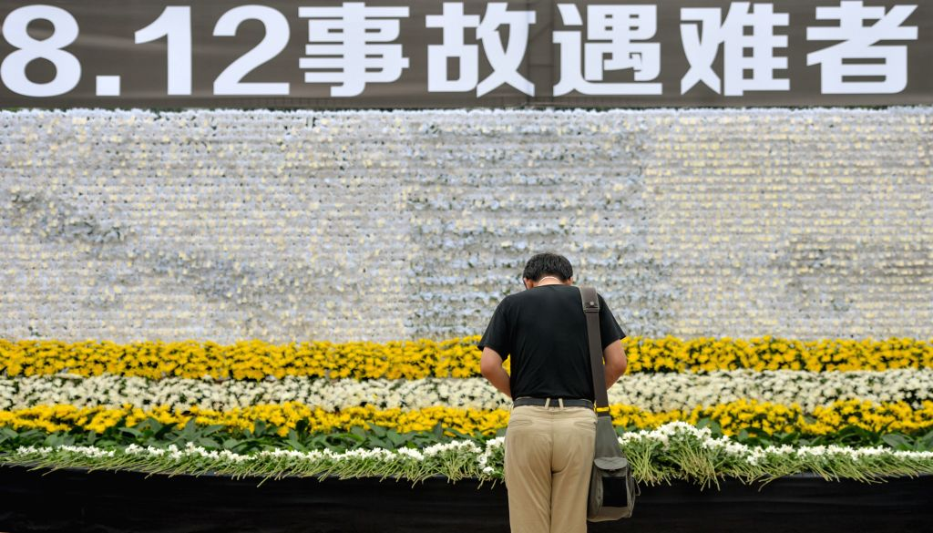 A man mourns for the victims of the massive warehouse explosions during a mourning ceremony held at a street park in the Binhai New Area of Tianjin, north China, ...