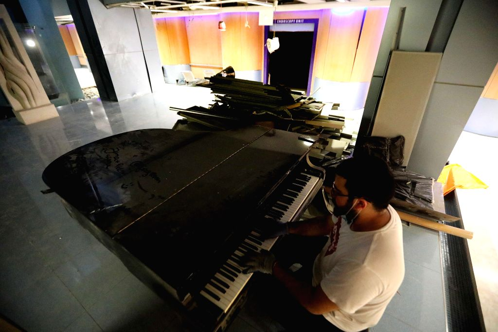 A man plays the piano in a destroyed hospital during a break of cleaning the explosion ruins in Beirut, Lebanon, Aug. 7, 2020. The death toll in the huge explosions ... - Hamad Hassan