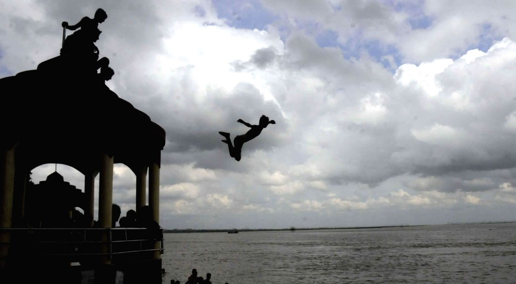 A man plunges into Ganga river on the last Monday of the holy month of Sawan in Patna on Aug 4, 2014.