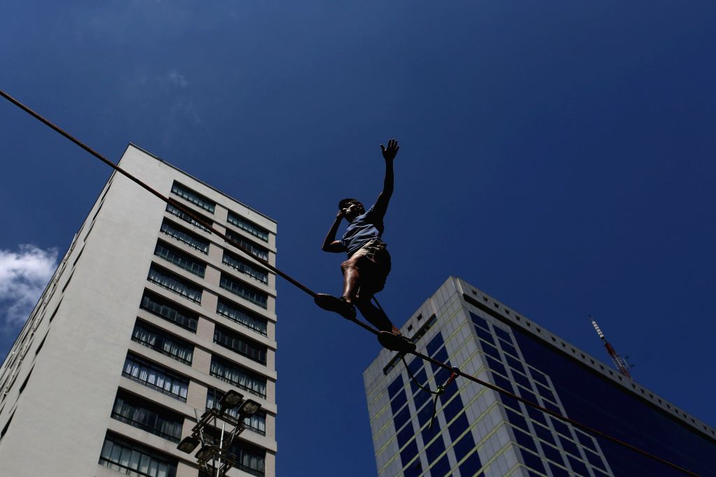"""A man practises the """"slackline"""" (tightrope), in Sao Paulo, Brazil, on Jan. 17, 2016. Beyond soccer, in the beaches and parks of Brazil, more and more ..."""