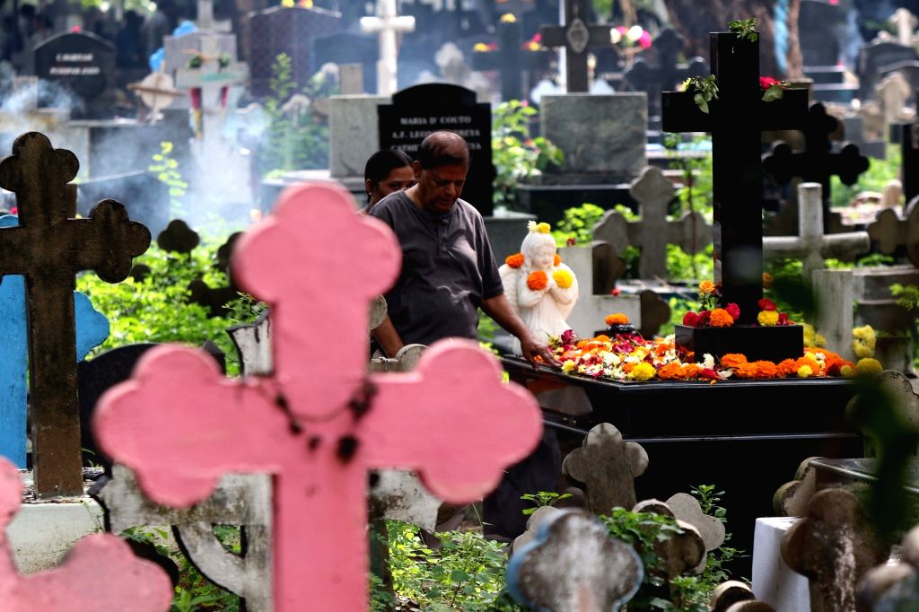 A man prays besides the grave of his relative at a cemetery during the observance of All Souls' Day in Chennai, on Nov 2, 2018.