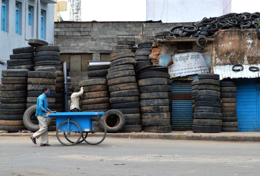 A man pushes an empty cart as he walks past a deserted street at Kalasipalya area during a strict lockdown that has been re-imposed for 15 days in five wards across Bengaluru to contain ...