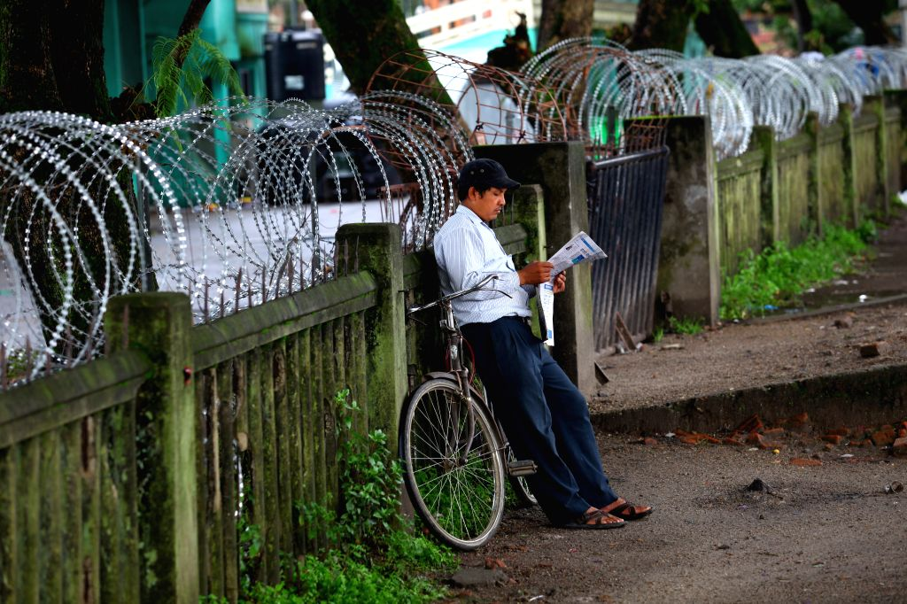 A man reads newspaper on the second day of a general strike called by alliance of 30 opposition parties led by UCPN-Maoist in Kathmandu, Nepal, Aug. 17, 2015. ... - Sunil Sharma