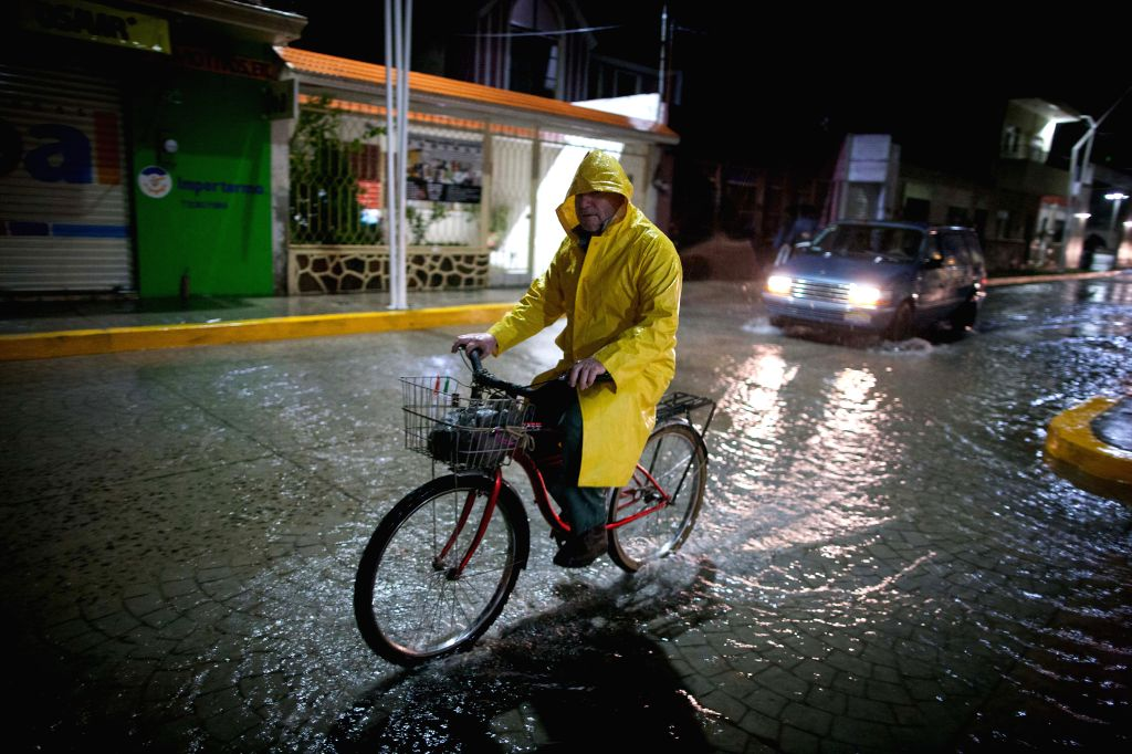 """A man rides his bicycle in the rain caused by the huricane """"Patricia"""" in Ameca, Jalisco state, Mexico, on Oct. 23, 2015. An hour after Hurricane Patricia ..."""