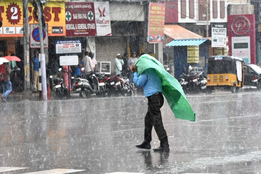 A man shields himself with a plastic sheet during rains in Hyderabad on Sep 30, 2019.