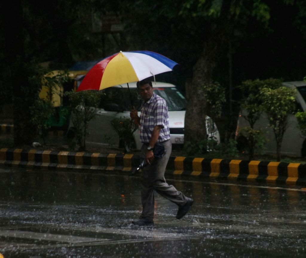 A man shields himself with an umbrella as rains lash Delhi on July 16, 2018.