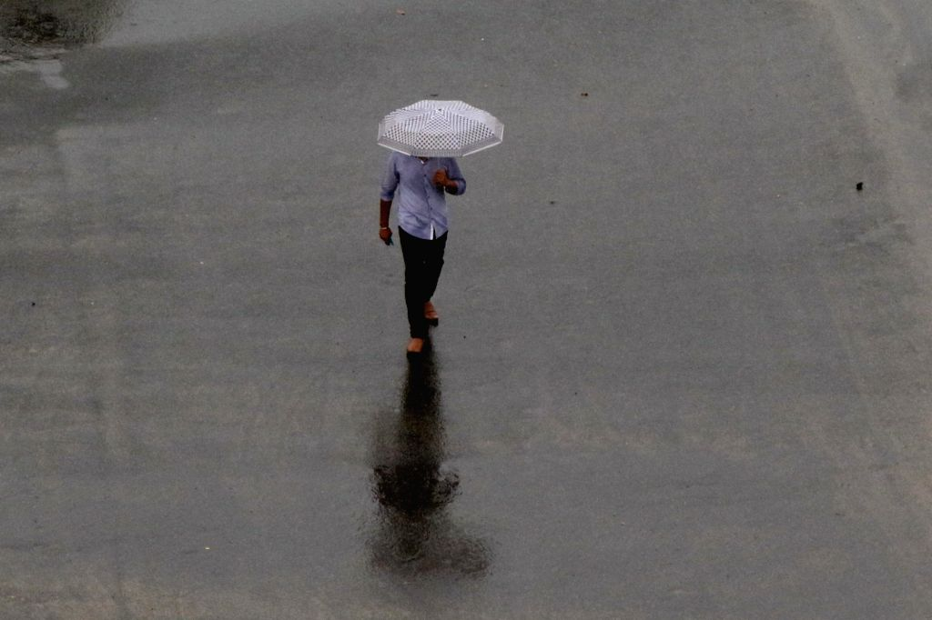 A man shields himself with an umbrella during rains, in Chennai on Oct 17, 2019.
