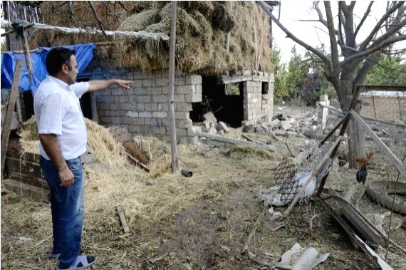 A man shows a house damaged during the new round of Nagorno-Karabakh conflict between Azerbaijan and Armenia in Fuzuli district of Azerbaijan, Sept. 30, 2020.