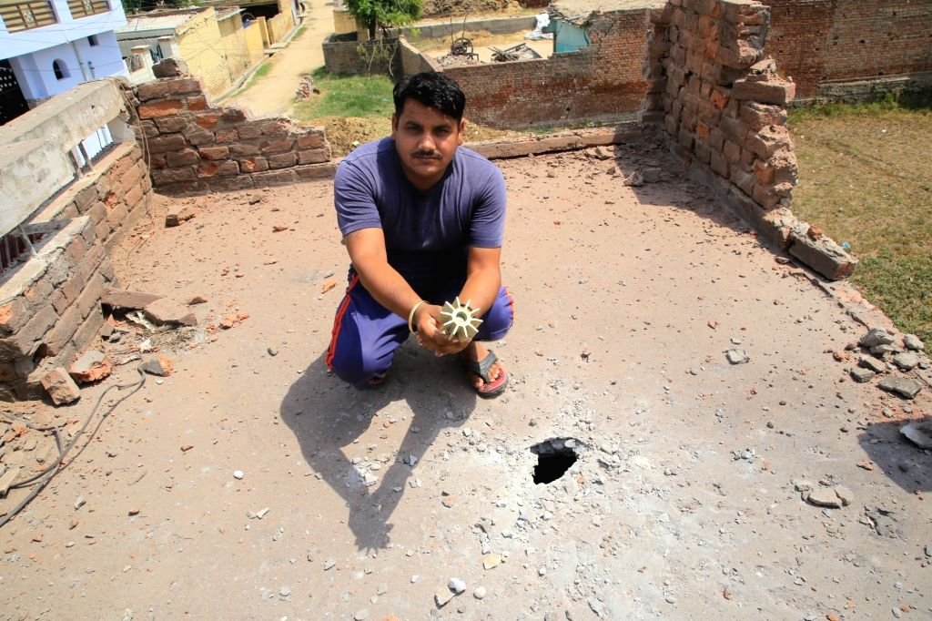 A man shows a part of a mortar shell, in Jammu on May 22, 2018. The Pakistani Rangers on Tuesday continued shelling on the international border (IB) in the Jammu and Samba districts of Jammu ...