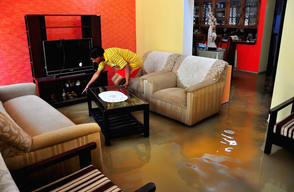 A man shows his drawing room that was flooded after heavy rains lash Bengaluru on Aug 15, 2017.