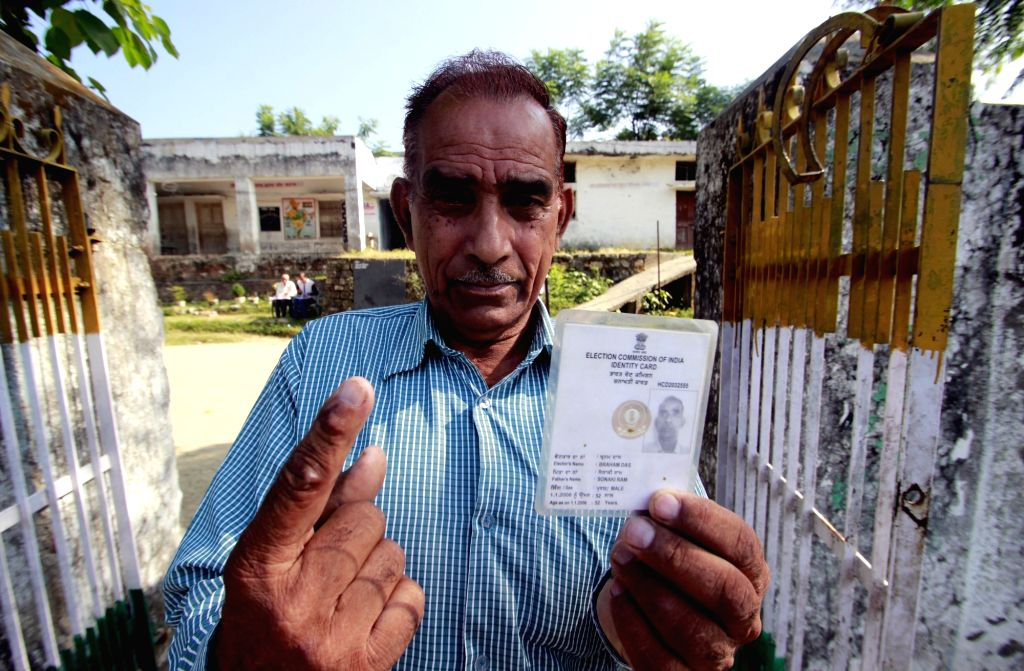 A man shows his inked finger and Voter ID Card  after casting vote for Gurdaspur Lok Sabha bypoll in Pathankot, Punjab on Oct 11, 2017.
