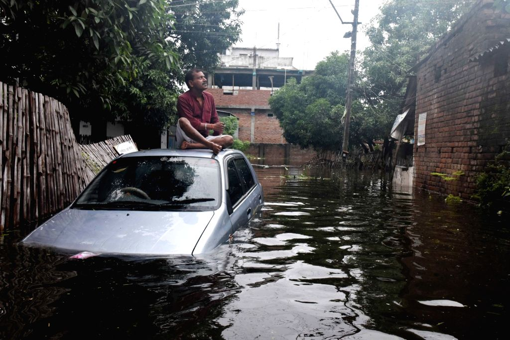 A man sits on a car submerged in flood water in Patna, on Sep 30, 2019.