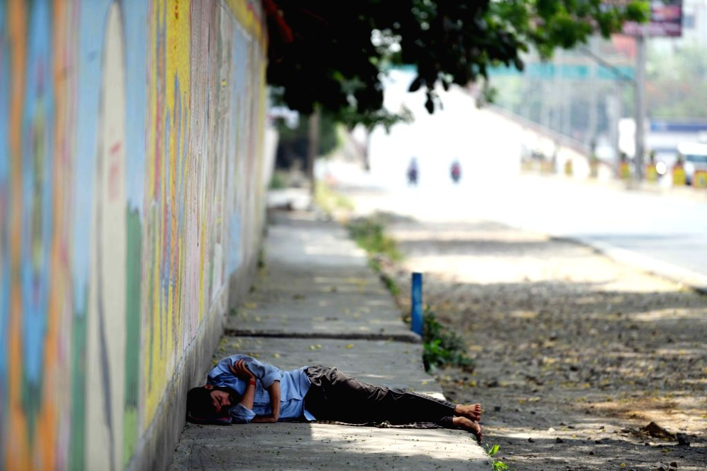 A man sleeps at a footpath along a deserted Patna street during the extended nationwide lockdown imposed to mitigate the spread of coronavirus; on Apr 25, 2020.