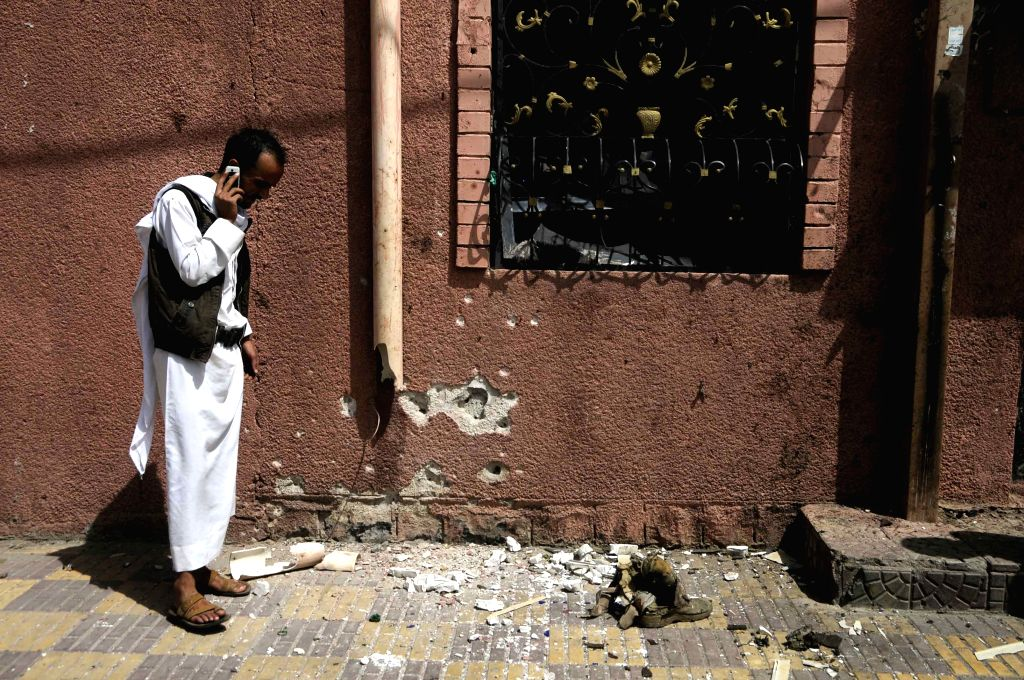 A man stands at the blast site outside the Saba news agency in Sanaa, Yemen, on June 25, 2015. An explosive device went off outside Yemen's state-run Saba news agency ...