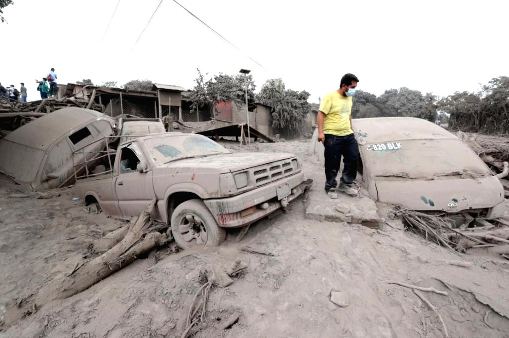 A man stands by damaged vehicles covered by ash in San Miguel Los Lotes, a village in Escuintla, Guatemala, on June 4, 2018. The death toll from the ...