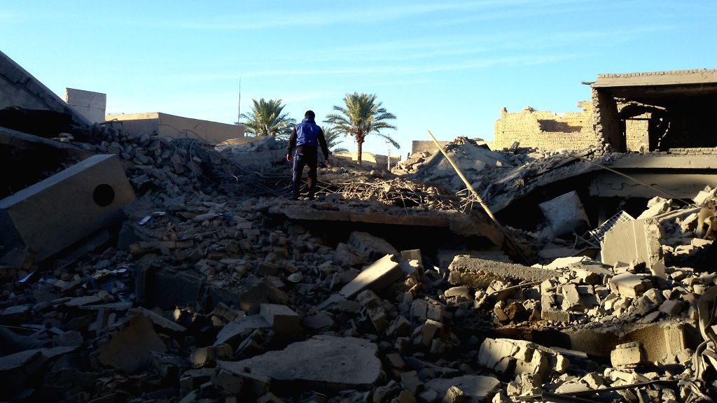 A man stands by destroyed buildings after an airstrike by the Iraqi Air Force in Islamic State (IS) militants-seized city of Fallujah, some 50 kilometers west of ...