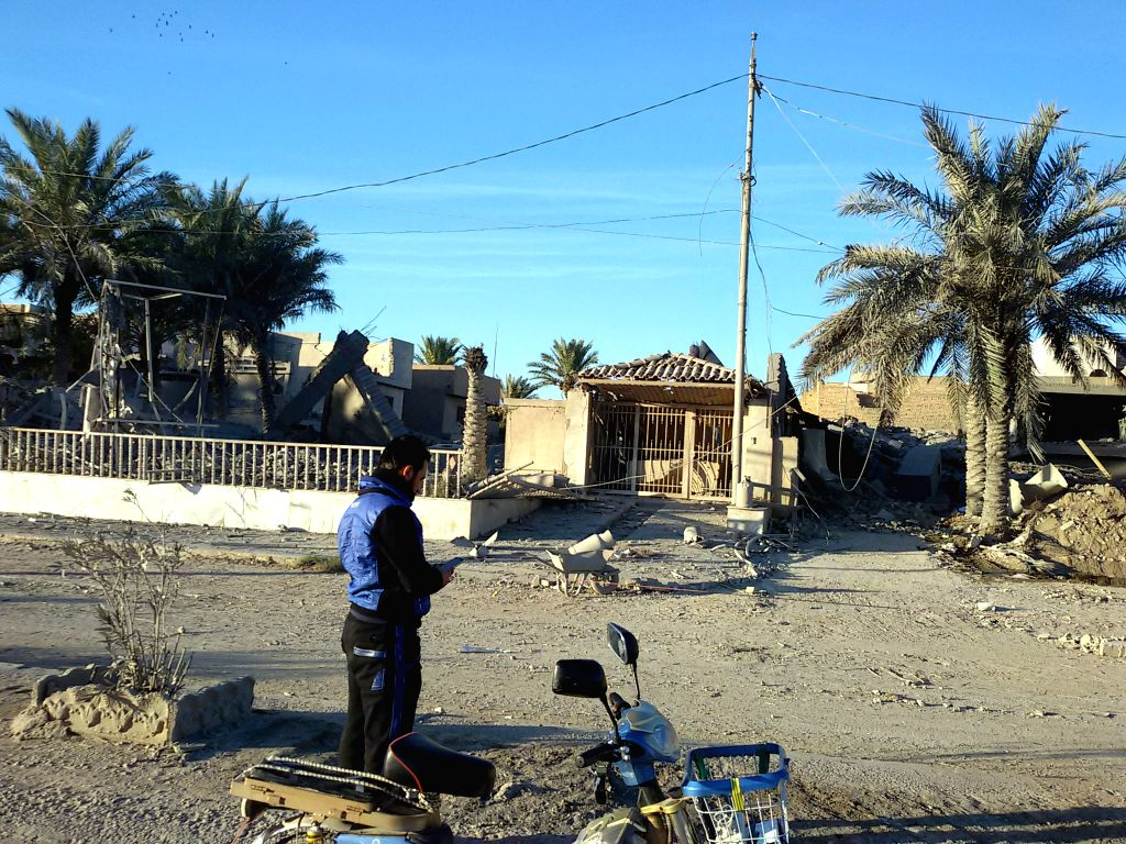 A man stands in front of destroyed buildings after an airstrike by the Iraqi Air Force in Islamic State (IS) militants-seized city of Fallujah, some 50 kilometers ...