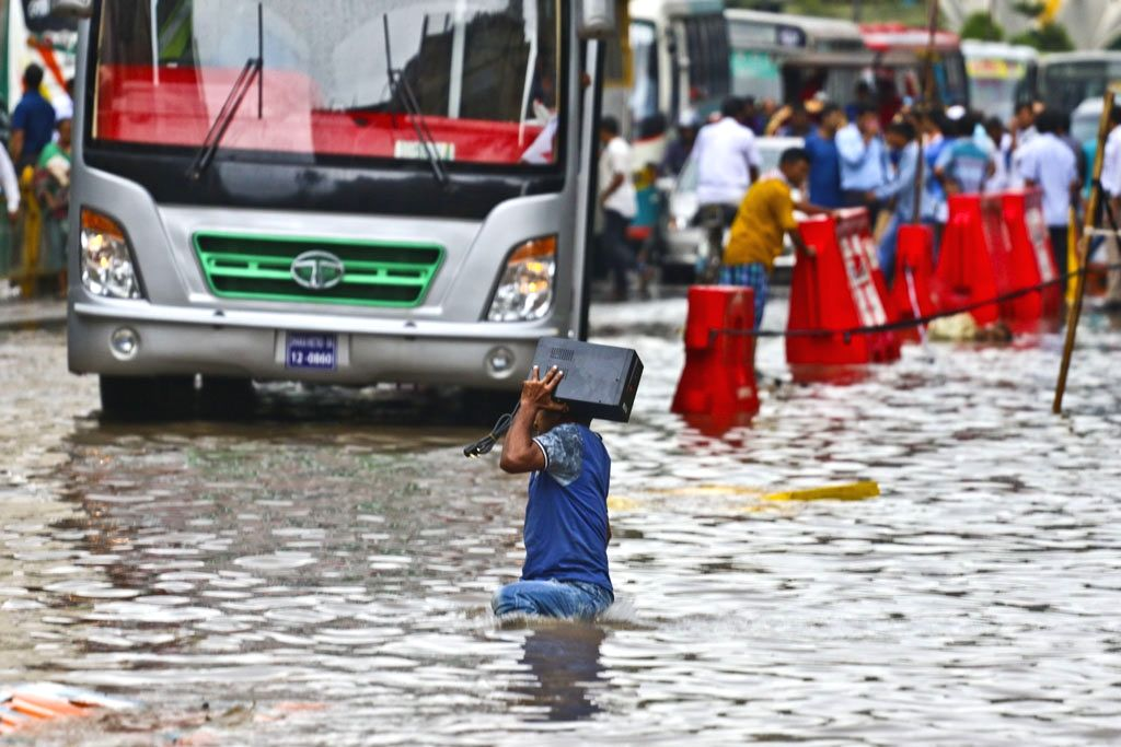 A man struggles through a waterlogged street after heavy rains lashed Dhaka, in Bangladesh on July 23, 2018.