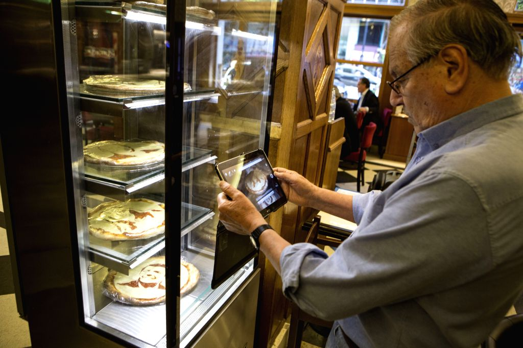 """A man takes a photo of pizzas with the faces of presidential candidates at the """"Los 36 Billares"""" pizza restaurant, in Buenos Aires city, Argentina, ..."""