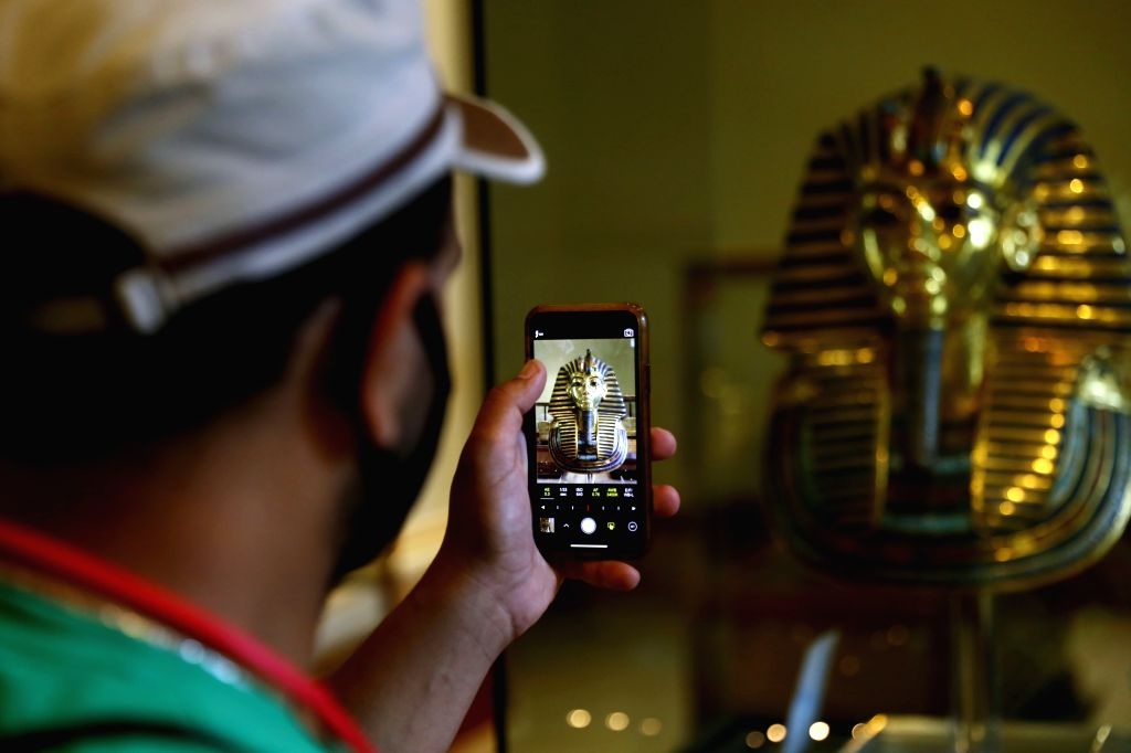 A man takes photos of the golden mask of King Tutankhamun at Egyptian Museum in Cairo, Egypt, on July 1, 2020. Egypt reopened on Wednesday the Egyptian Museum, the ...