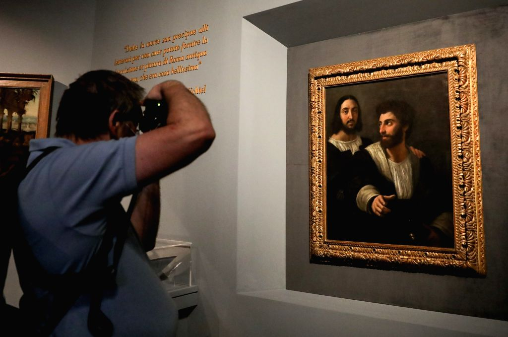 "A man takes pictures of a painting during the exhibition ""Raffaello 1520-1483"" in Rome, Italy, July 2, 2020. The ""Raffaello 1520-1483"" exhibition, ..."