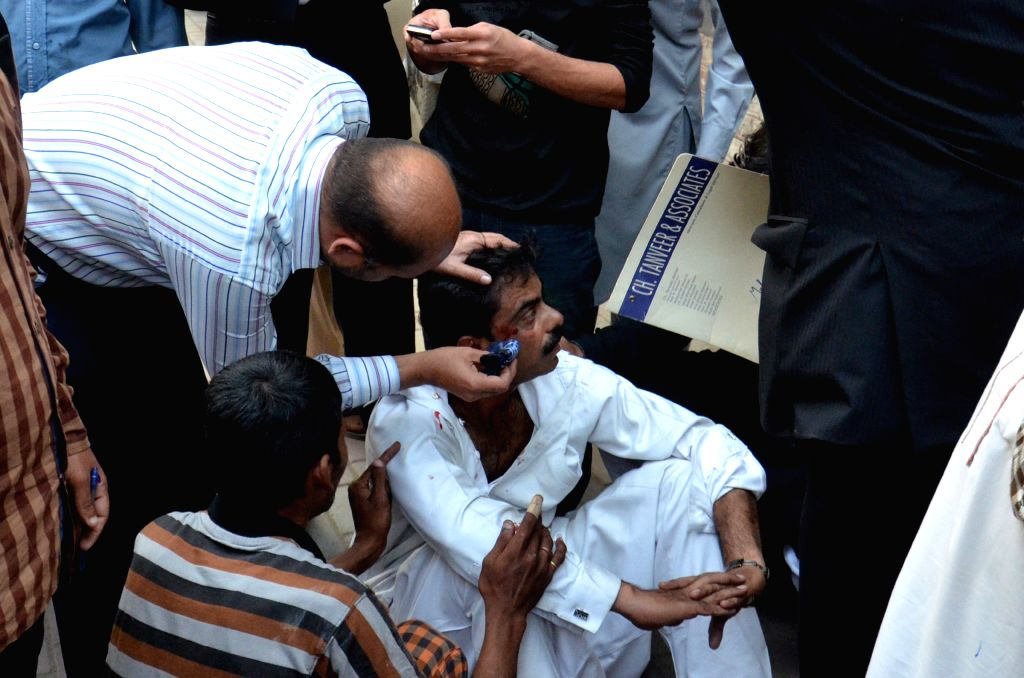 A man treats an injured man after a severe earthquake in eastern Pakistan's Lahore on Oct. 26, 2015. At least 125 people were killed and over 1,000 others injured ...