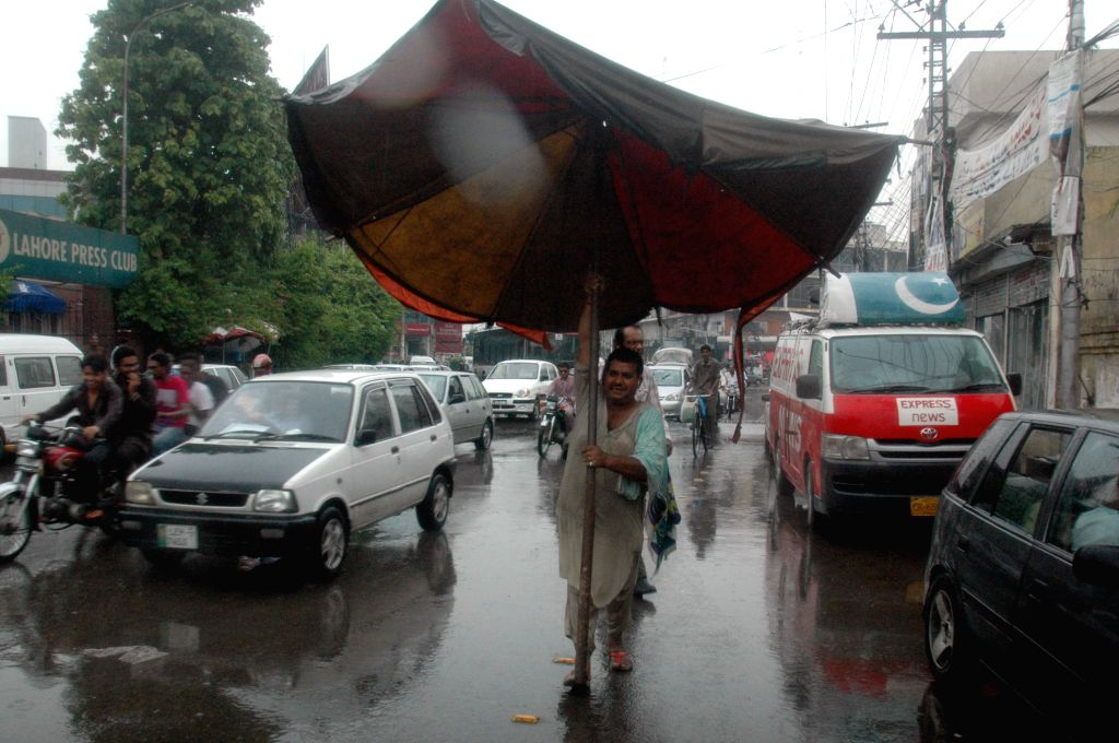A man tries to set up an umbrella in heavy rain in eastern Pakistan's Lahore, July 24, 2015. An estimated 285,000 people have been affected by floods in Chitral ...