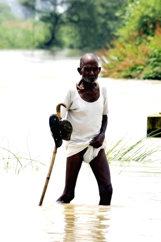 A man wades through flood waters in Patna district of Bihar on Aug 19, 2014.