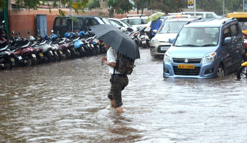A man wades through water logged streets of Panaji after pre monsoon showers lashed the city  on May 31, 2017.