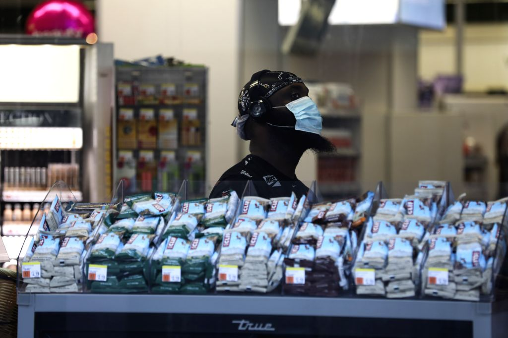 A man waits at the checkout counter of a grocery store in New York, the United States, July 29, 2020. U.S. COVID-19 deaths have surpassed the 150,000 mark to reach ...