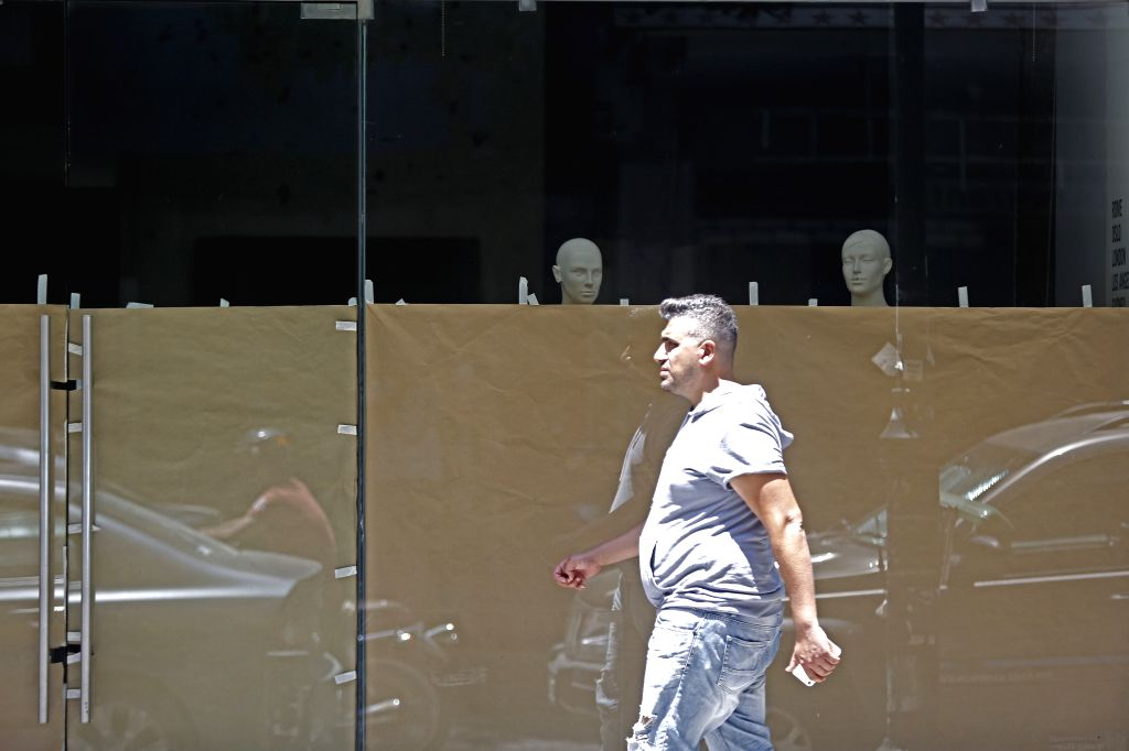 A man walks by a closed shop in Beirut, Lebanon, July 2, 2020. Lebanon's number of COVID-19 infections increased on Thursday by eight to 1,796 while the death toll ...