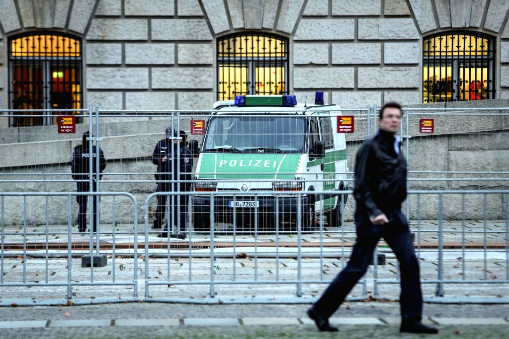 A man walks by guarding police officers outside the Reichstag building in Berlin, Germany, on Nov. 14, 2015. Security officials in Germany have taken necessary ... - Thomas