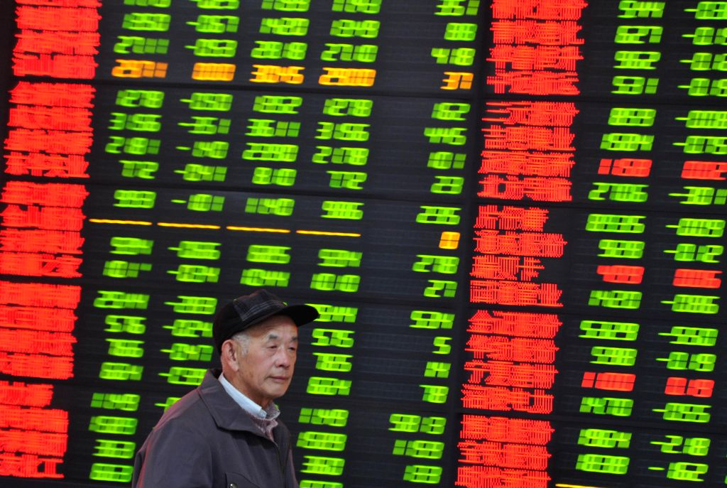 A man walks past an electronic display showing Hong Kong's Hang Seng Index, which fell, to close at 23,485.83 points, compared with the previous trading day closed down 561.84 points, down by 2.34 per cent. Full-day total turnover of HK $ 144.2 billi