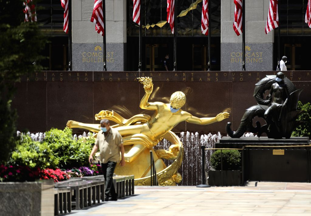A man walks past statues with face masks at Rockefeller center in New York, the United States, July 4, 2020. The number of COVID-19 cases in the United States ...