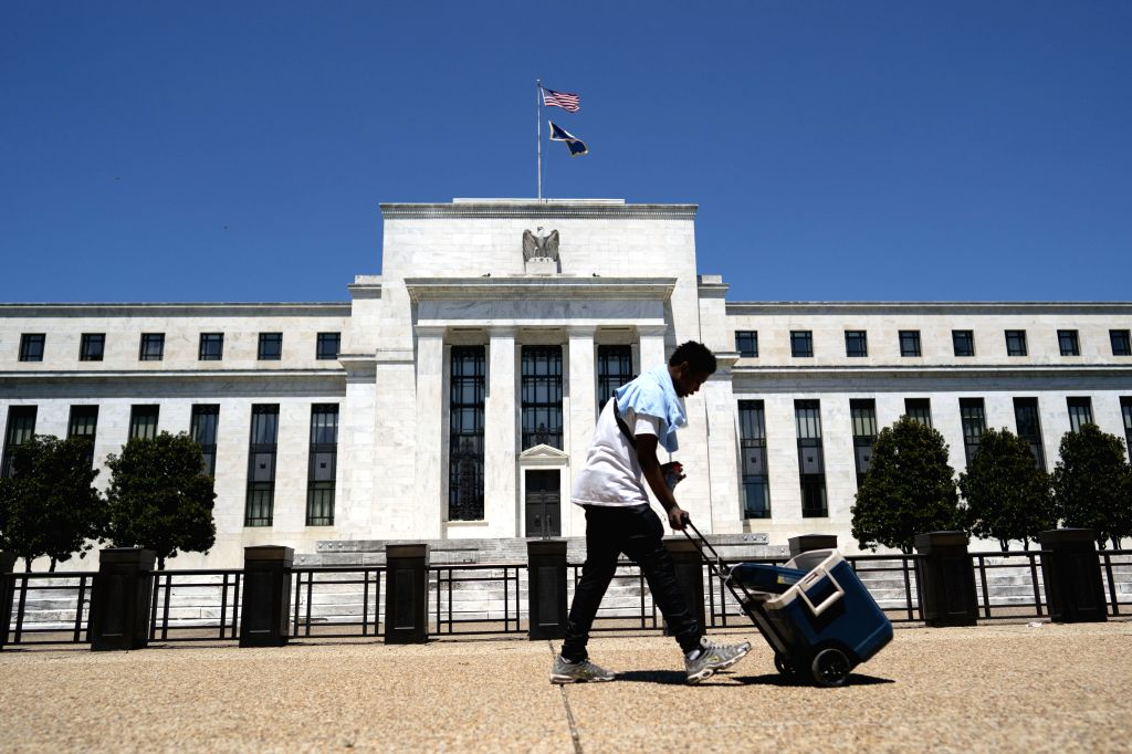 A man walks past the U.S. Federal Reserve building in Washington, D.C., the United States, July 29, 2020. The U.S. Federal Reserve on Wednesday kept its ...