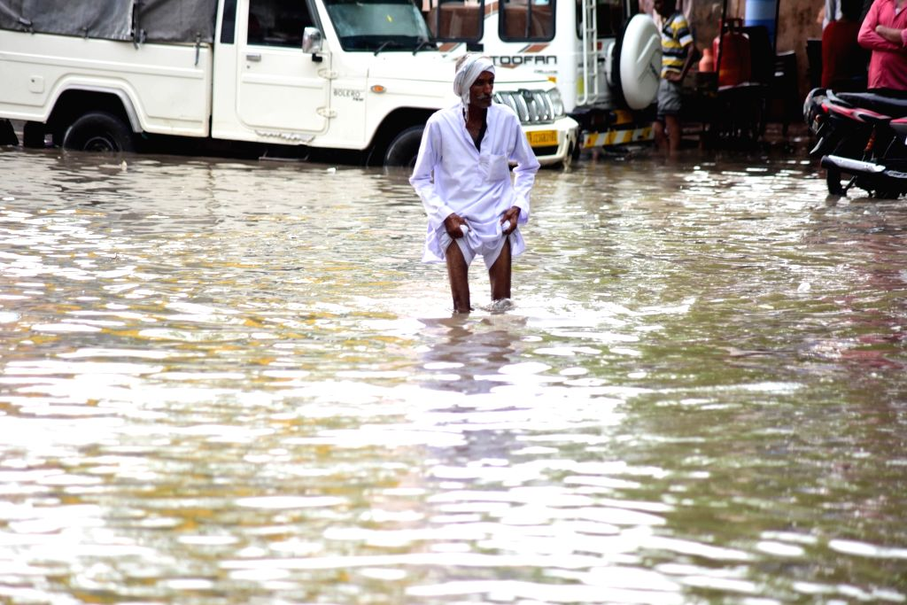 A man walks through a water-logged street after heavy rains, in Bikaner on July 17, 2018.