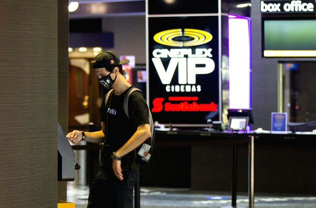 A man wearing a face mask buys a ticket from a self-serve kiosk outside a reopened movie theater in Toronto, Canada, on July 31, 2020. The City of Toronto entered ...