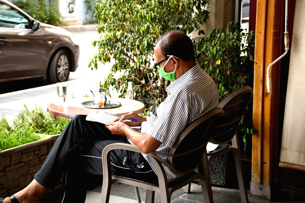 A man wearing a face mask plays word puzzle at a cafe in Rabat, Morocco, June 25, 2020. Morocco started on Thursday relaxing pandemic restrictions by allowing people ...