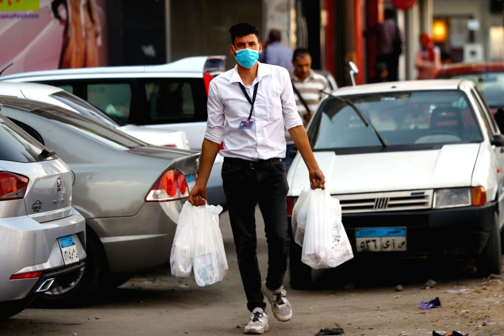 A man wearing a face mask walks on a street in Cairo, Egypt, on Aug. 12, 2020. Egypt confirmed on Wednesday 129 new COVID-19 infections, bringing the total cases ...