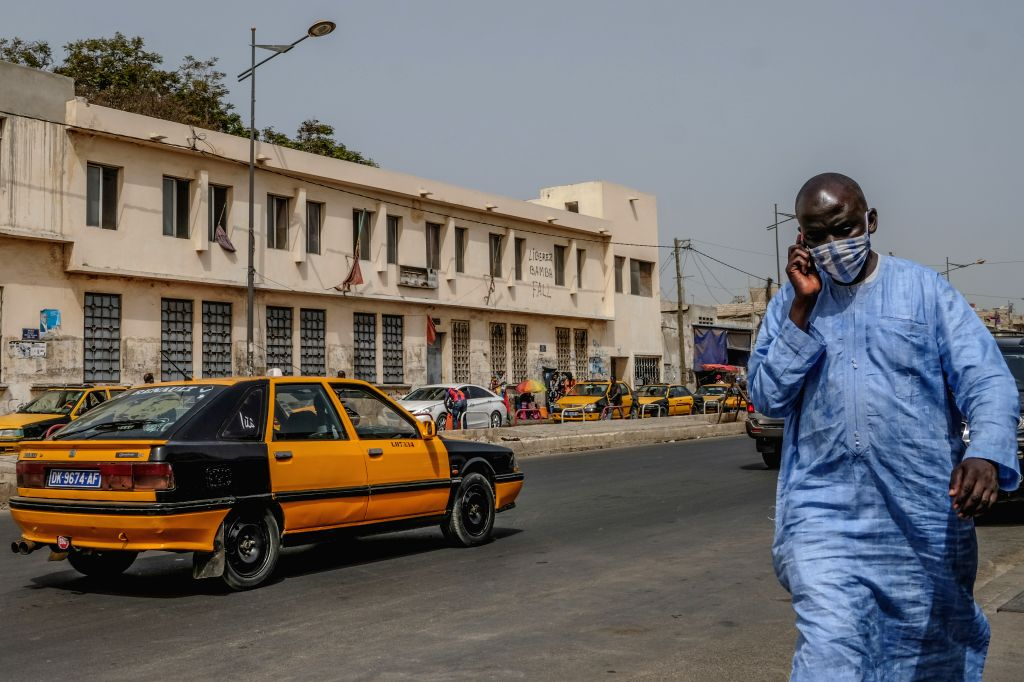 A man wearing a mask walks on a street in Dakar, Senegal, on July 1, 2020. Four months after the outbreak of the COVID-19 pandemic on March 2 in Senegal, the country's ...