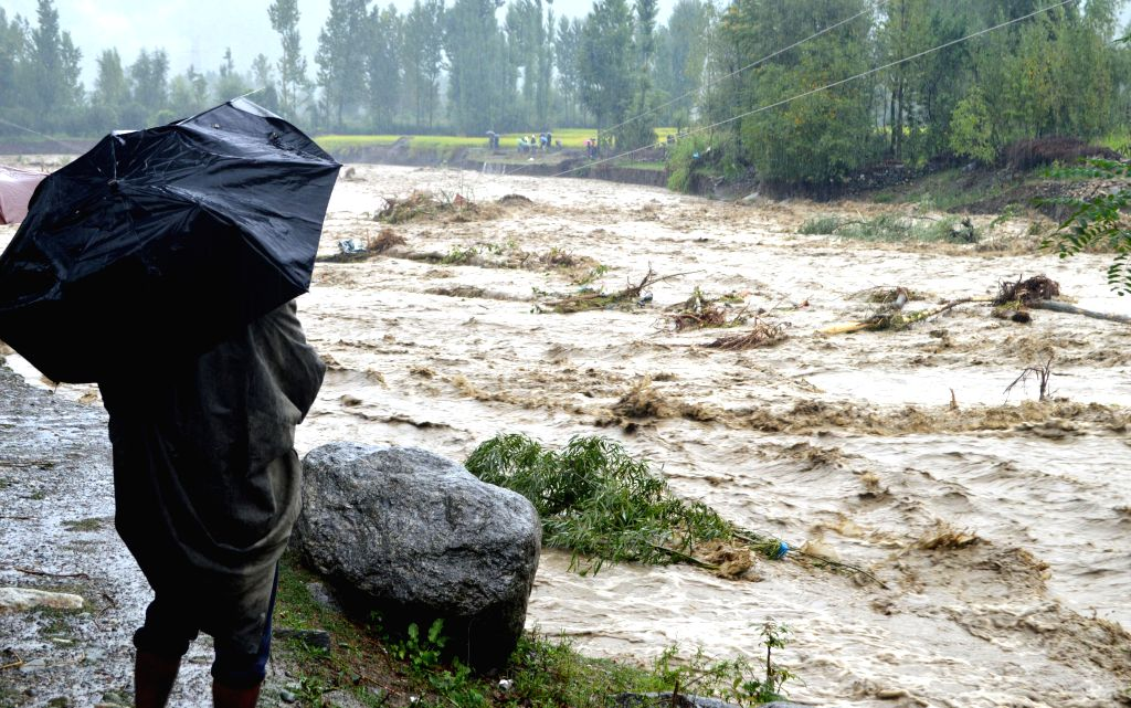 A man with an umbrella watches the flood water at Baramulla in North Kashmir on Sept. 6, 2014.