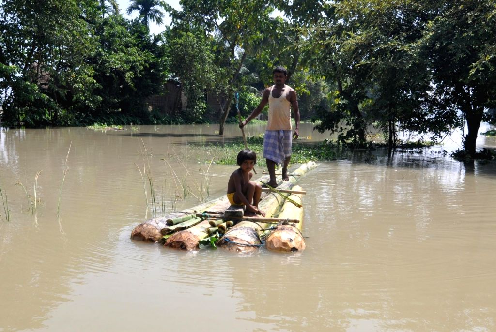 A man with his child rows in a makeshift banana raft through flood hit areas in Assam's Morigaon district, on Sept 16, 2018.